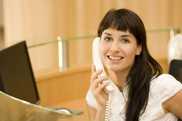 photo of a smiling receptionist answering the phone