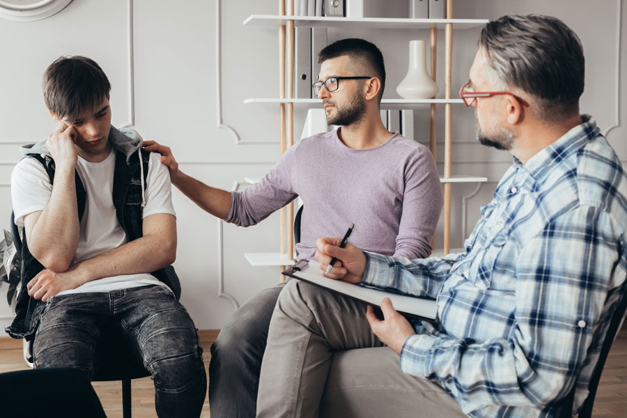 a father and a depressed-looking son talking to a male counselor